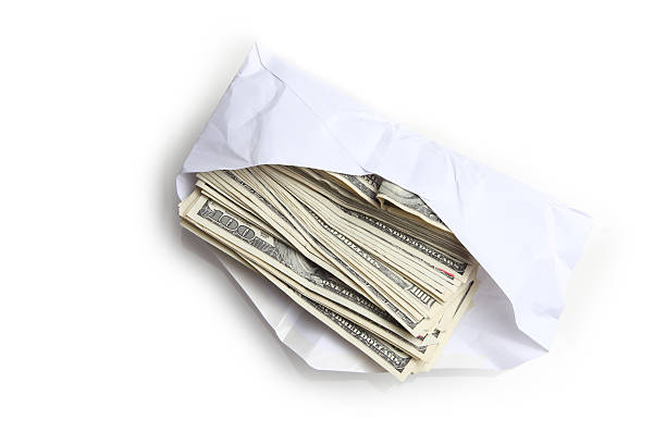 Envelope filled with stack of hundred dollar bills stock photo