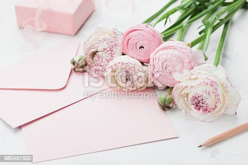 680461500 istock photo Envelope or letter, paper card, gift and pink ranunculus flowers. Greeting on Mothers or Womans Day. 680461500
