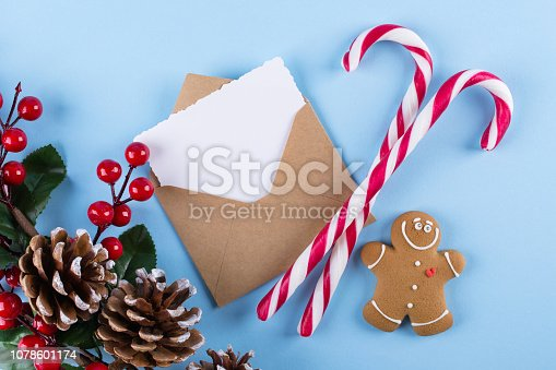 istock Envelope, paper card and decoration on blue table top view. Christmas mockup for greeting. Flat lay. Merry Chraistmas and happy new year 1078601174