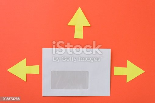 istock Envelope with arrows in different directions, orange background 928873258