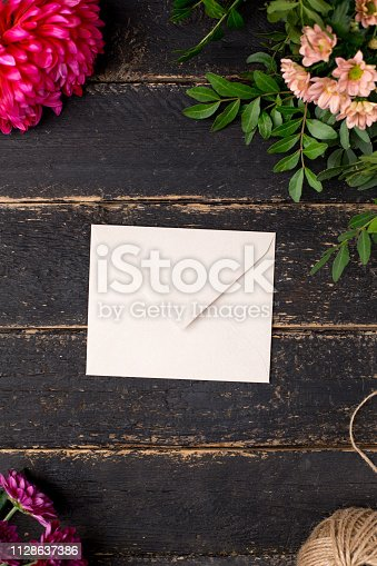 680461500 istock photo Envelope with beautiful flowers on a dark vintage table 1128637386