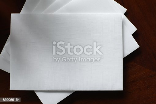istock Envelope With Blank Note on Wooden Material 859066154