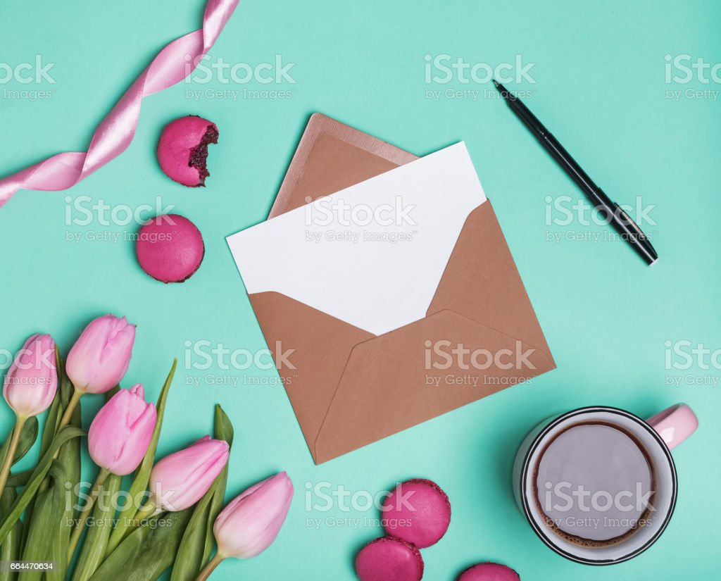 Envelope with blank paper, pen, coffee and flowers stock photo