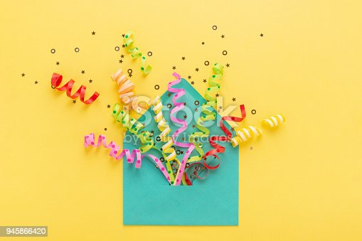 istock Envelope with party confetti explosion on yellow background. Invitation card, flat lay. 945866420