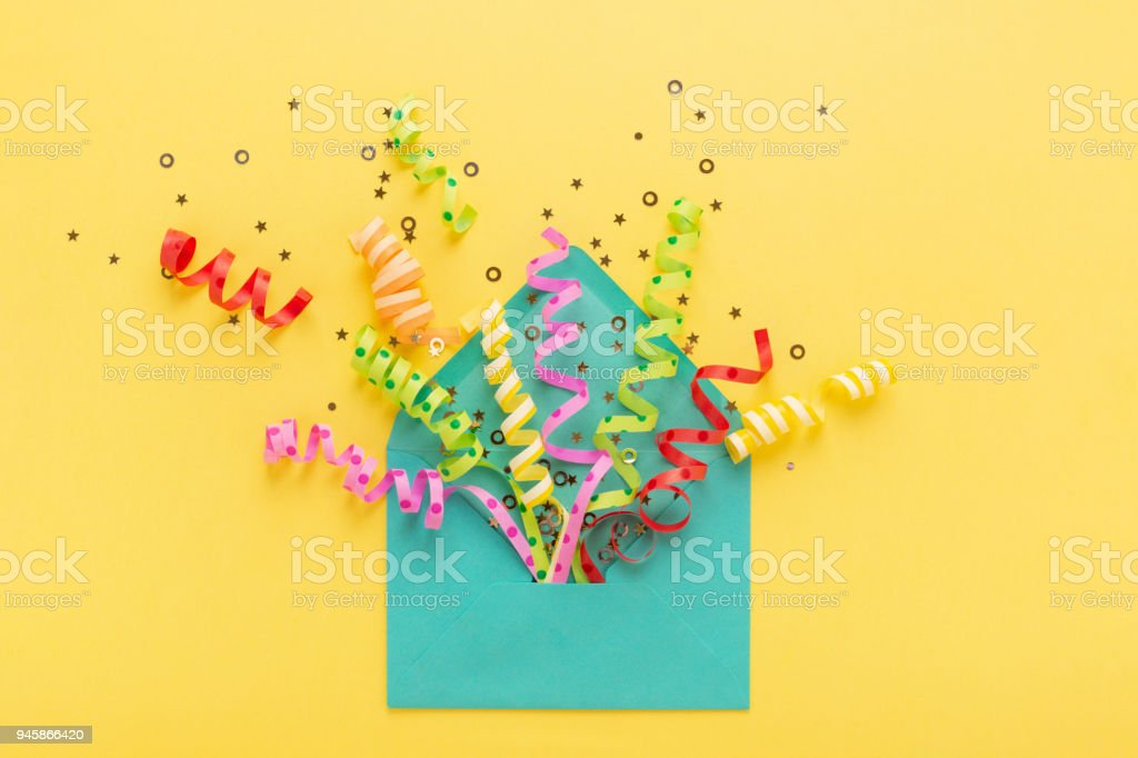 Envelope with party confetti explosion on yellow background. Invitation card, flat lay. stock photo