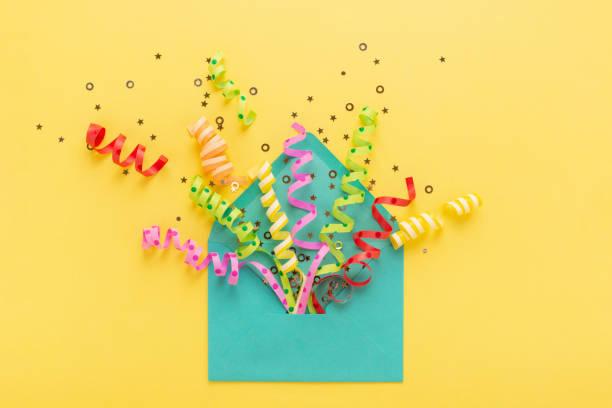 umschlag mit party-konfetti-explosion auf gelbem hintergrund. einladungskarte, flach legen. - originelle geburtstagsgeschenke stock-fotos und bilder