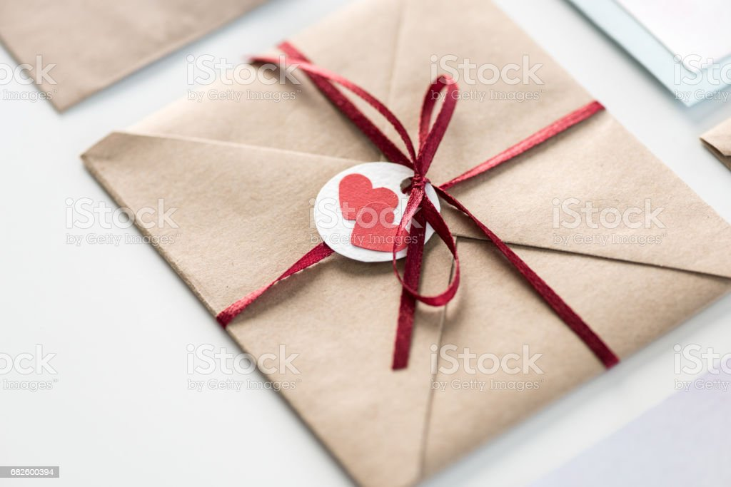 Envelope With Tag With Two Hearts And Ribbon Isolated On White