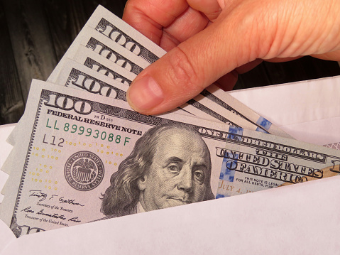 Woman pulls money out of an envelope, wages, bribe or savings concept