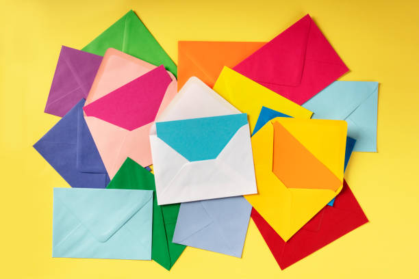C6 envelopes of various colors, shot from the top on a yellow background stock photo