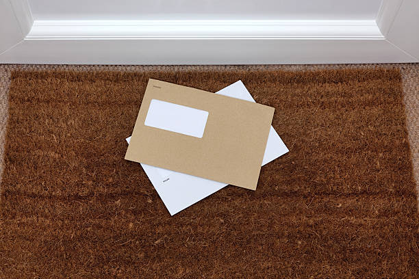 Envelopes on the doormat Two envelopes on a doormat, blank window to add your own name and address details. letterbox format stock pictures, royalty-free photos & images