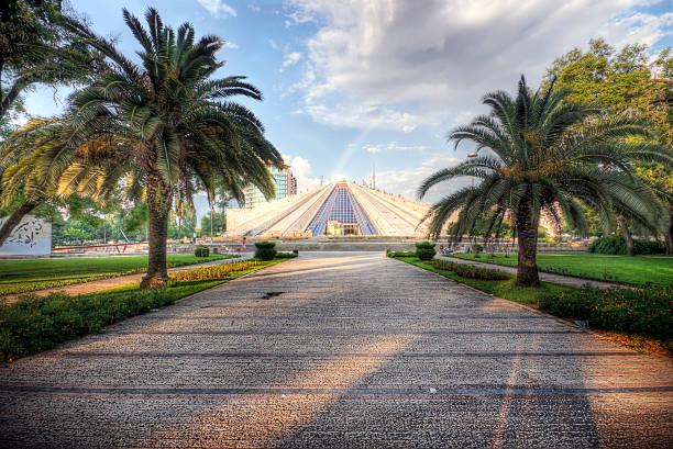 Enver Hoxha Pyramid in Tirana Tirana Albania: This national symbol was erected in 1985 by the daughter of the former communist dictator Enver Hoxha, with intentions of building a museum honoring the life of her father. Today the building awaits renovation and a new function. A rainbow can be seen emerging from right behind the pyramid after a brief rain storm. Photo processed for high dynamic range. davelongmedia stock pictures, royalty-free photos & images