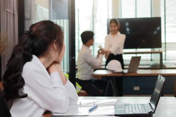 嫉妬怒っているアジア ビジネスの女性は、オフィスで恋愛情カップルを探しています。友人関係で羨望と嫉妬 - 羨望 ストックフォトと画像