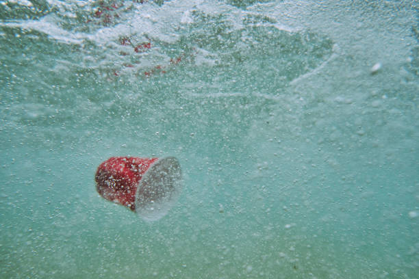 enviromental issues, red used single use plastic cup in the sea. - trash stock pictures, royalty-free photos & images