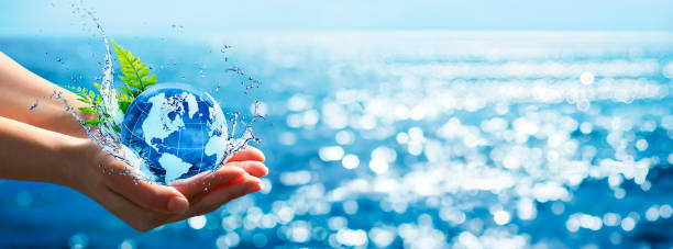 Environment Concept - Hands Holding Globe Glass In Blue Ocean With Defocused Lights stock photo