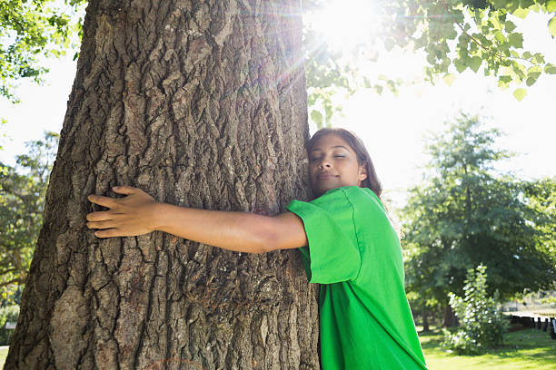 Environmental activist hugging a tree in the park Environmental activist hugging a tree in the park on a sunny day tree hugging stock pictures, royalty-free photos & images