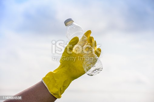 Image of adult hand with yellow color glove and empty plastic bottles. Blue Sky background.