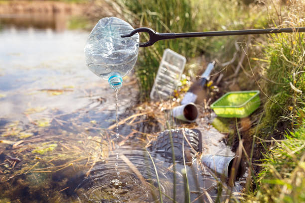 Environmental conservation collecting garbage and trash from water stock photo