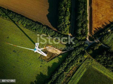 Aerial view of a wind turbine and cultivated fields