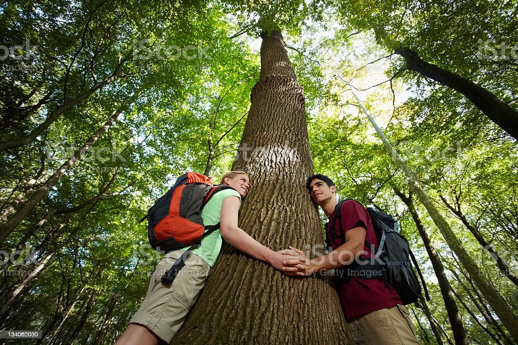 environmental conservation: young hikers embracing large tree royalty-free stock photo