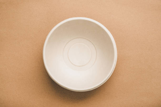 environmental eco friendly natural compostable food container round shape bowl on recycled brown paper - biodegradabile foto e immagini stock