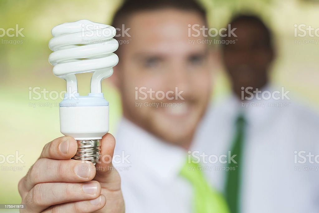 Environmental issues; corporate responsibility; business man holding energy efficient lightbulb stock photo