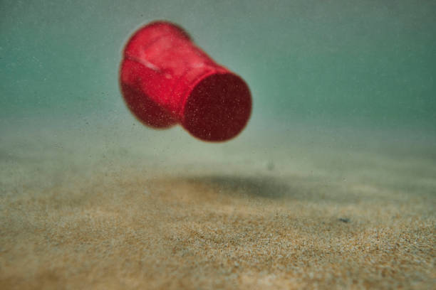 environmental issues, used single use red plastic cup floating in shallow sea. - trash stock pictures, royalty-free photos & images