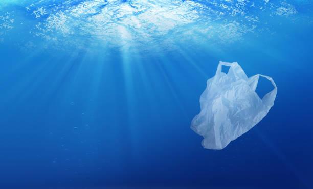 environmental protection concept. plastic bag pollution in ocean - biodegradabile foto e immagini stock