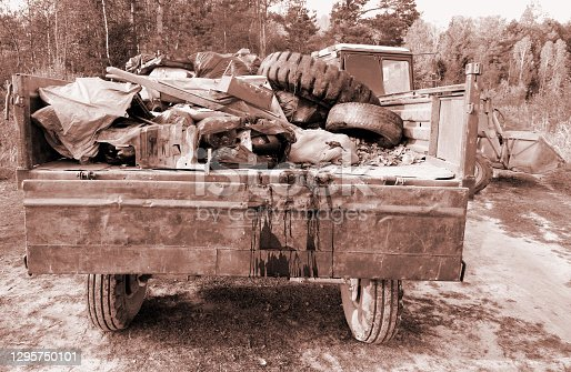 Environmental protection. Tractor takes out garbage after cleaning up forest. Sepia toning