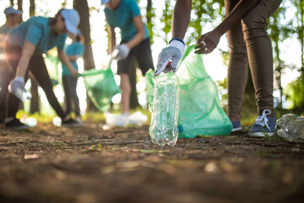 Environmental Volunteers Unrecognizable people cleaning up the park from garbage environmental cleanup stock pictures, royalty-free photos & images