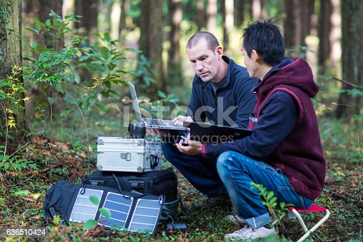 Two environmentalists or scientists monitor the forest with a solar powered field laboratory