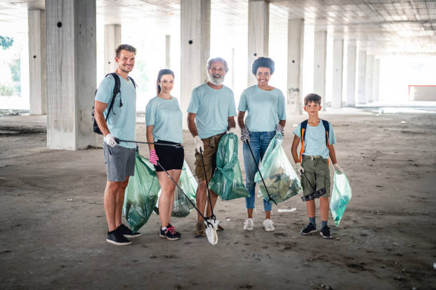 Environmentalists with Tools for Cleaning Up Outdoor Garage Mixed age group of responsible citizens with trash grabbers and bags of garbage looking at camera in outdoor garage. social responsibility stock pictures, royalty-free photos & images
