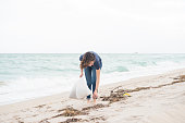 This is a horizontal, full frame, color photograph of a beautiful, socially conscious Millennial woman of Israeli descent at Haulover Beach in Miami, Florida, USA. Carrying plastic bags she looks along the shore to clean up trash littered on the beach. She wears jeans and a blue t-shirt as she walks barefoot on the sand during a windy, winter day along the Atlantic Ocean.