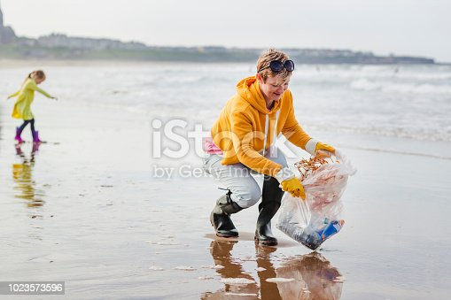 Collecting rubbish off a beach. Plastic containers, bottles in their bag. Women picking up rubbish from the waters edge.