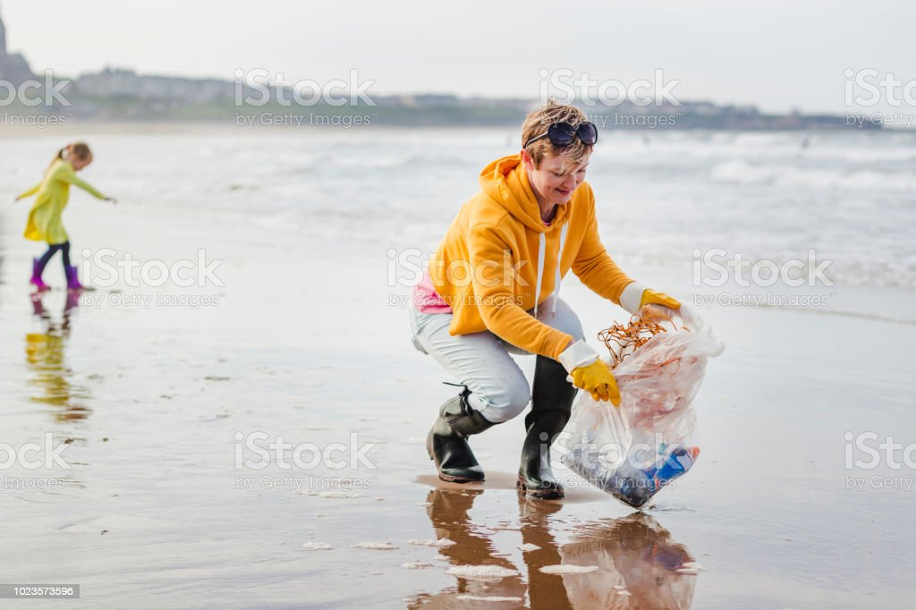 Environmentally Conscious Woman Cleans Up Beach stock photo
