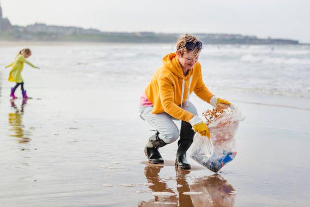 Environmentally Conscious Woman Cleans Up Beach Collecting rubbish off a beach. Plastic containers, bottles in their bag. Women picking up rubbish from the waters edge. environmental cleanup stock pictures, royalty-free photos & images