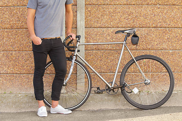 Environmentally friendly transport A cropped shot of a young man standing next to a bicycle skinny jeans stock pictures, royalty-free photos & images
