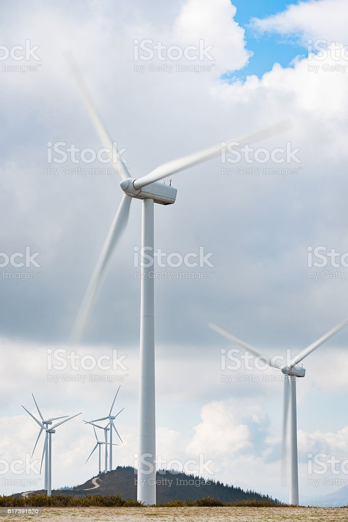 Environmentally friendly wind energy turbines farm in eolic rural park stock photo
