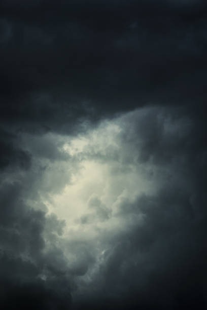 epic clouds with bright spot in the middle - dramatic sky stock pictures, royalty-free photos & images