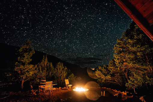 Long Exposure Photo of a Modern A-Frame Tiny Home at Night with Millions of Bright Stars on a Clear Night in the Summer. One Chair Faces the Campfire.  This Tiny House Unaweep Canyon along Highway 141 in Western Colorado near Thimble Rock Point and Uncompahgre National Forest is a Unique Getaway for Travelers Wanting to Relax and Get