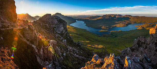 Epic sunrise over Highland peaks glens lochs wilderness panorama Scotland Golden sunrise illuminating the dramatic mountain peaks, glens and ridges of Coigach overlooking Loch Lugainn on the wild and remote peninsula deep in the Northwest Highlands of Scotland, UK. ProPhoto RGB profile for maximum color fidelity and gamut. scottish highlands stock pictures, royalty-free photos & images
