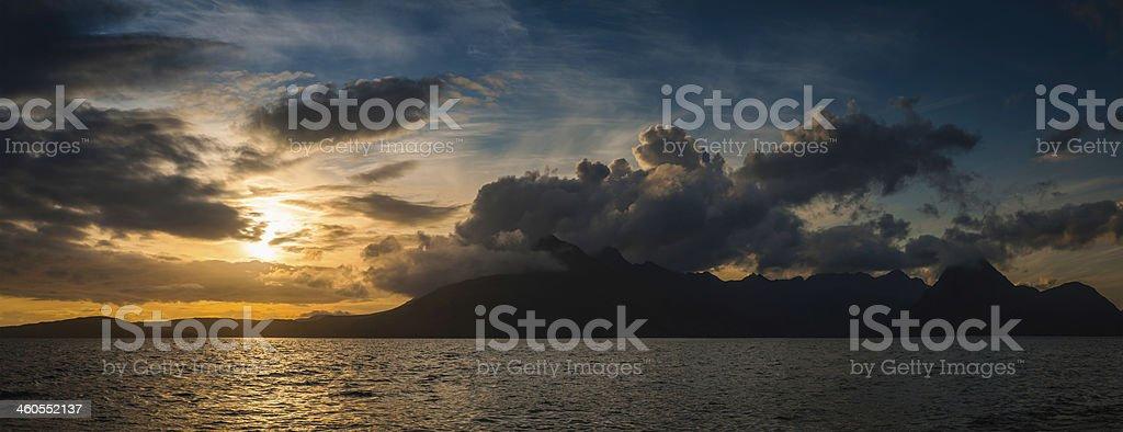 Epic sunset dramatic cloudscape over idyllic ocean mountain wilderness panorama stock photo