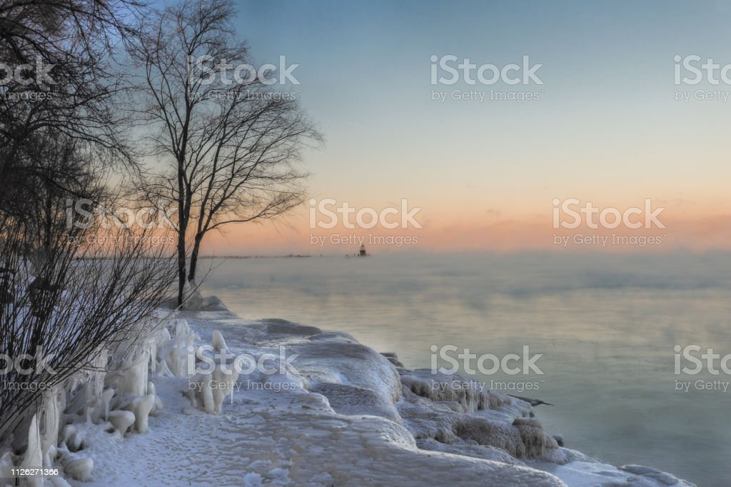 Epic sunset over freezing lake with snow and ice covered beach and...