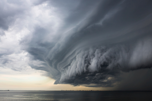 A mean looking huge storm cloud hovering over the ocean.