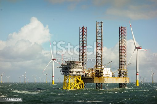 istock Epic view on Large offshore 8MW wind turbines, wind farm on the horizont in north sea with jack up boat and offshore platform in wavy sea 1253690396