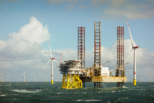 Epic view on Large offshore 8MW wind turbines, wind farm on the horizont in north sea with jack up boat and offshore platform in wavy sea