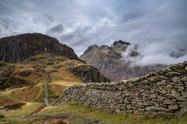 Epic Winter landscape image of view from Side Pike towards Langdale pikes with low level clouds on mountain tops and moody mist swirling around stock photo