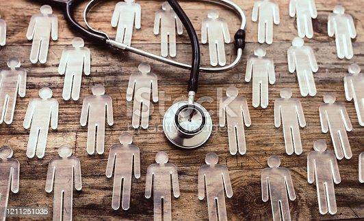epidemic or pandemic medicine concept -  many transparent figurines and stethoscope on wood background