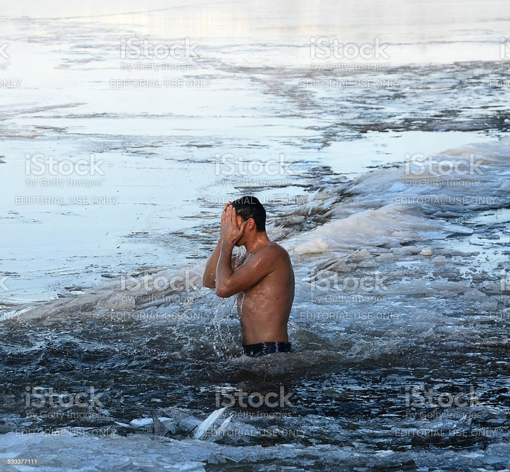 Epiphany bathing in the icy water of the river stock photo