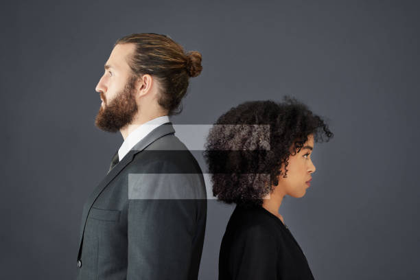 Equal means equal Shot of two corporate businesspeople posing together in studio with gender symbols inserted in the background social justice concept stock pictures, royalty-free photos & images