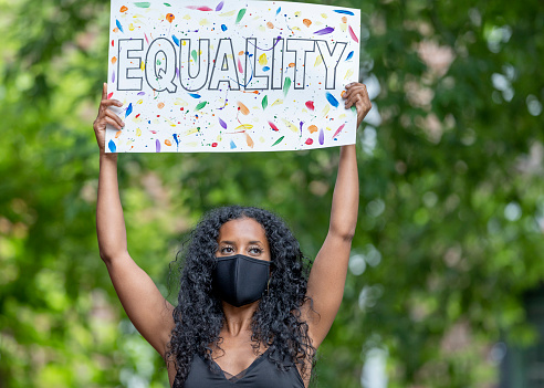 A beautiful young female adult of African ethnicity is standing outdoors. She is wearing a face mask and is holding a poster with the word